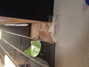 A glass tile is missing from the kitchen backsplash